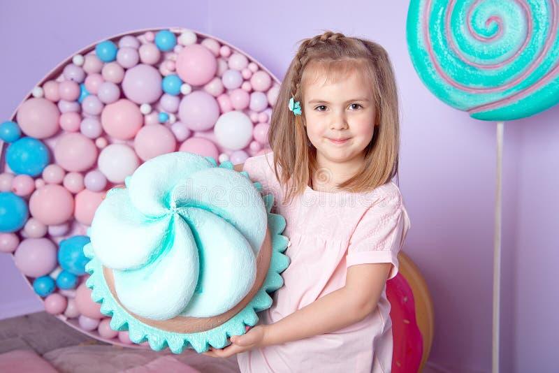 Menina que senta-se na sala colorida em torno dos doces toyful grandes, filhós, pirulito imagens de stock