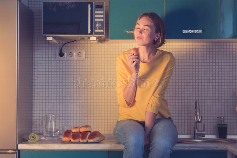 A menina que senta-se na tabela aprecia uma pastelaria deliciosa na noite Fa?a dieta o conceito imagem de stock royalty free