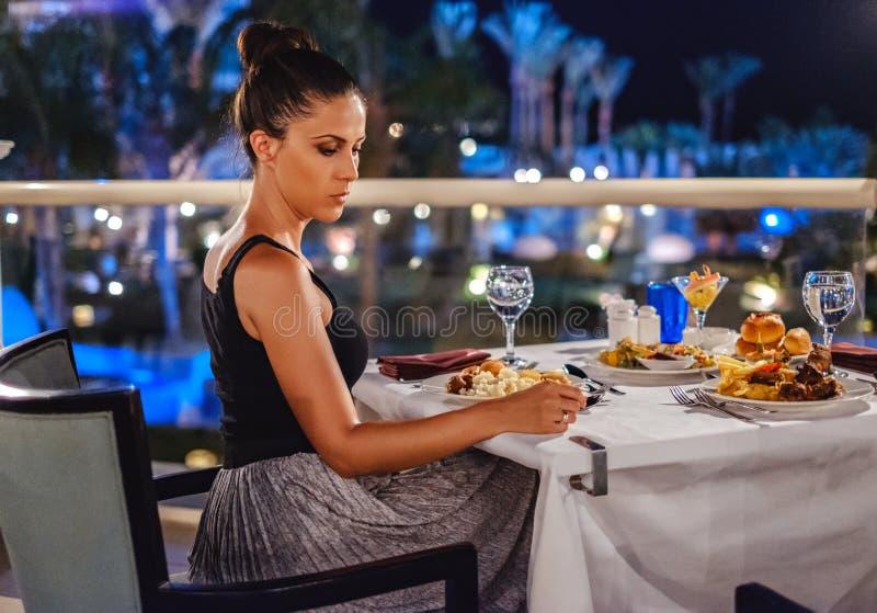 Menina que senta-se na tabela do restaurante e que olha tristemente para baixo imagem de stock