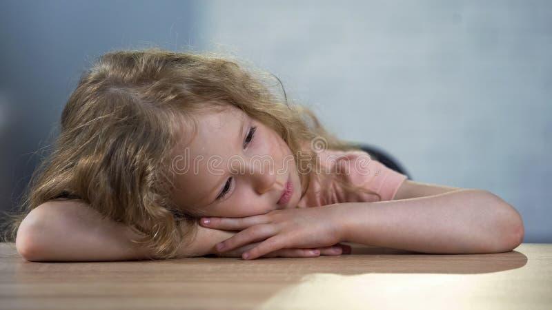 Menina que senta-se na tabela, tiranizando na escola, sonho órfão sobre a família imagem de stock