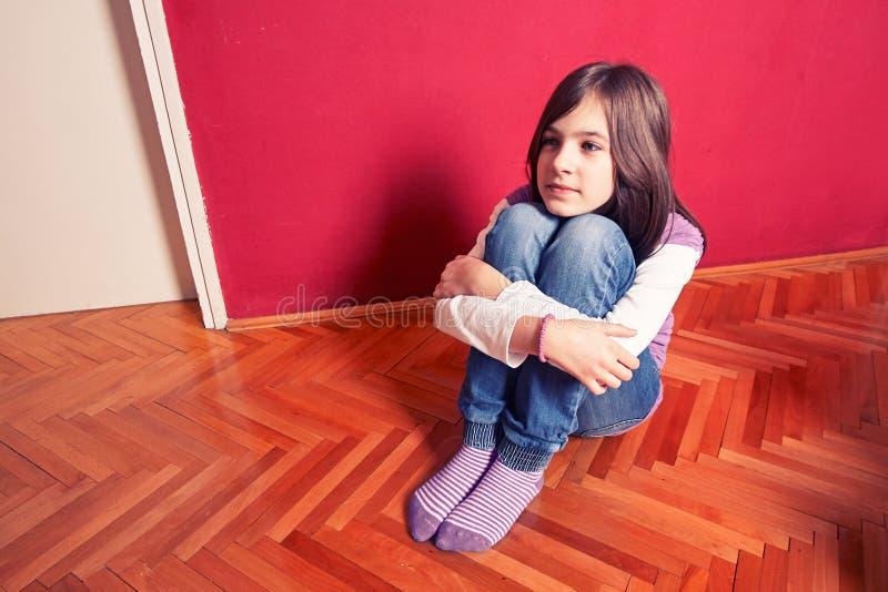 Menina que senta-se no assoalho imagens de stock