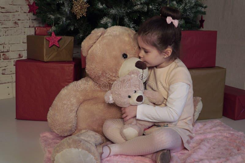 A menina que senta-se no assoalho com dois tamanhos diferentes brinca os ursos que esperam Santa na Noite de Natal foto de stock royalty free