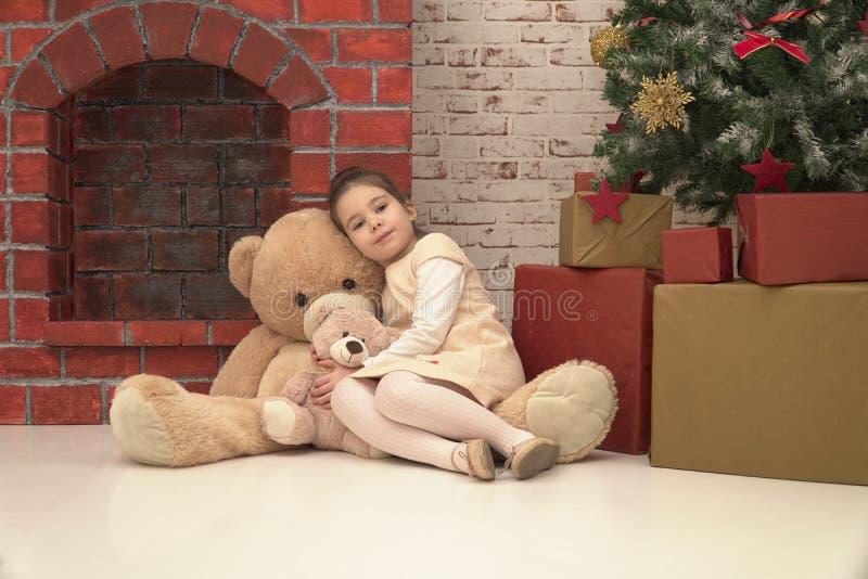 A menina que senta-se no assoalho com dois tamanhos diferentes brinca os ursos que esperam Santa na Noite de Natal fotografia de stock