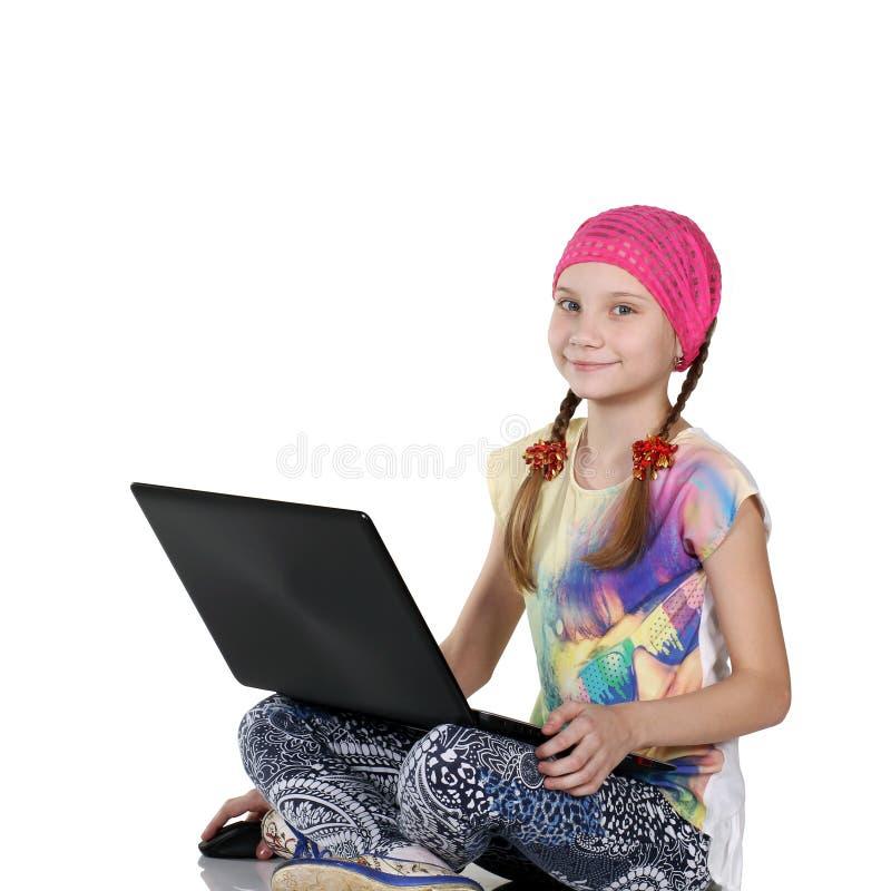 Menina que senta-se no assoalho, mostrando o laptop preto fotografia de stock