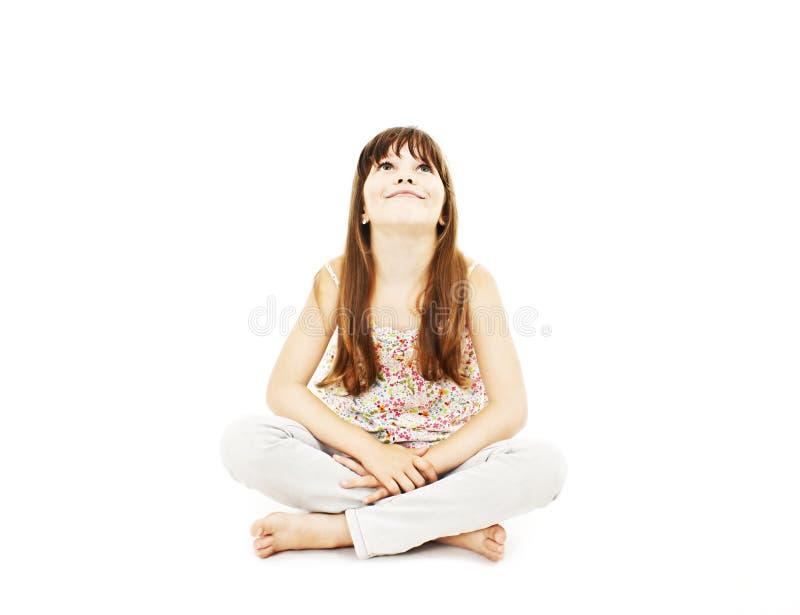 Menina que senta-se no assoalho, sorrindo e olhando acima fotografia de stock