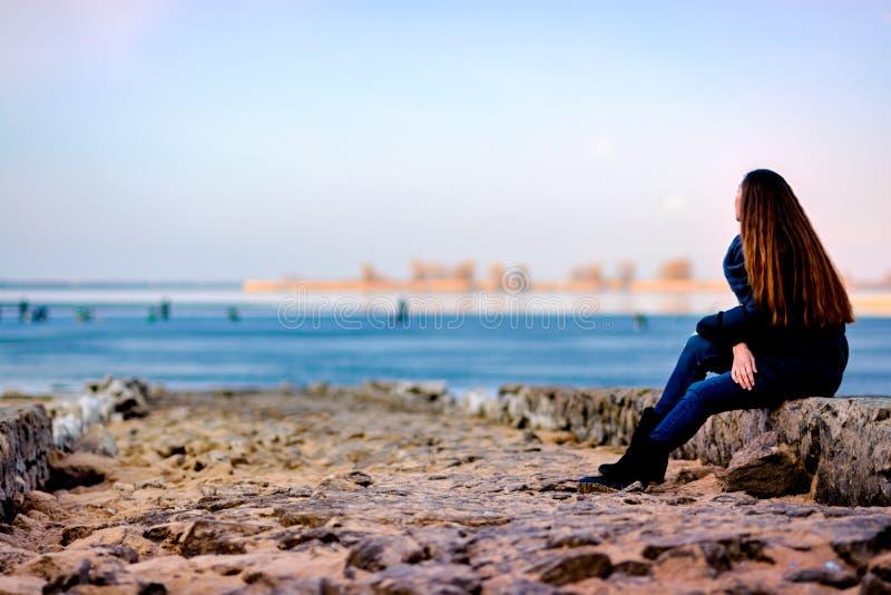 Menina que senta-se no banco do rio fotos de stock