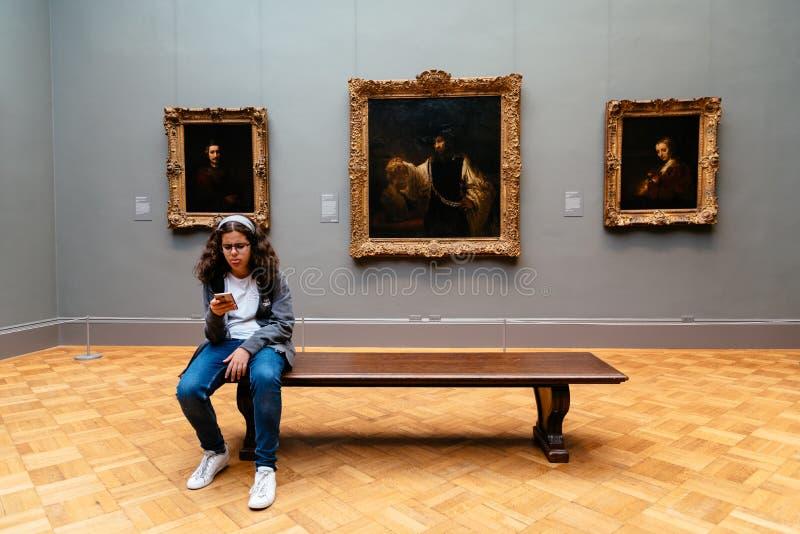 Menina que senta-se no banco no salão da pintura no museu fotografia de stock royalty free