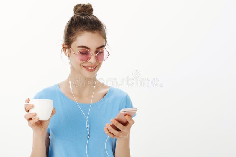 A menina que senta-se no café que fala ocasionalmente com amigo vie mensagens no smartphone, na música de escuta e no café bebend imagem de stock royalty free