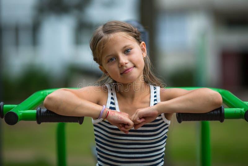 Menina que senta-se no equipamento do exercício no parque público fotografia de stock royalty free