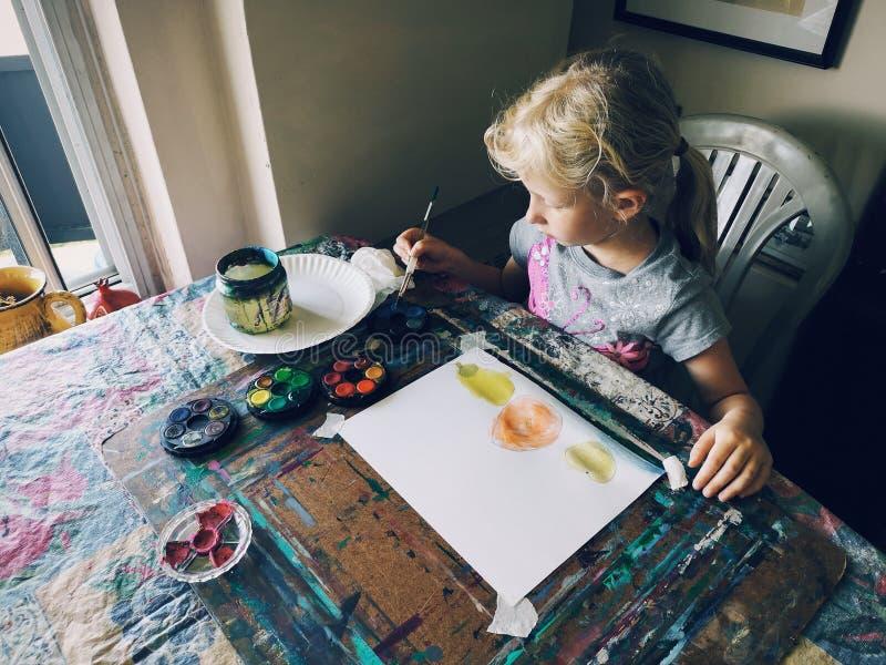 Menina que senta-se no estúdio da arte da casa concentrado em frutos de pintura com escovas e pinturas da aquarela imagem de stock royalty free