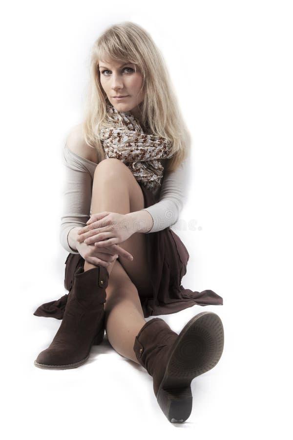 Menina que senta-se no fundo branco imagens de stock