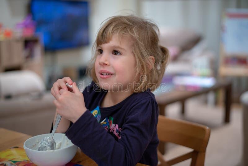 Menina que senta-se no muesli comer do café da manhã com o iogurte da bacia branca imagens de stock