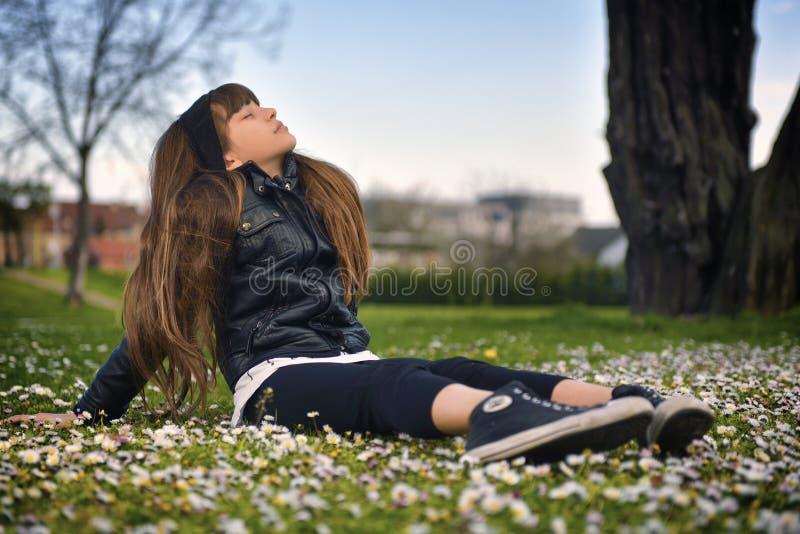 Menina que senta-se no parque fotografia de stock