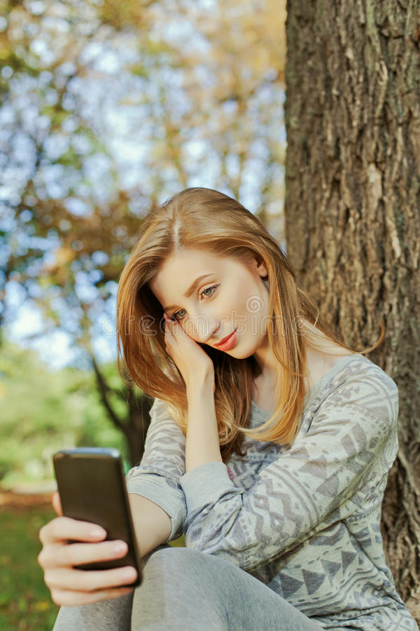 A menina que senta-se no parque e faz o selfie imagem de stock royalty free