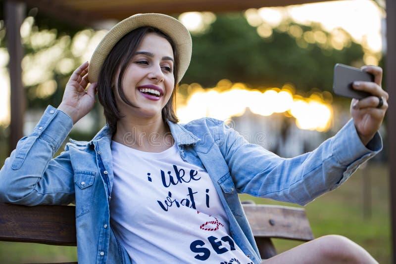 A menina que senta-se no parque e faz o selfie, feliz foto de stock royalty free