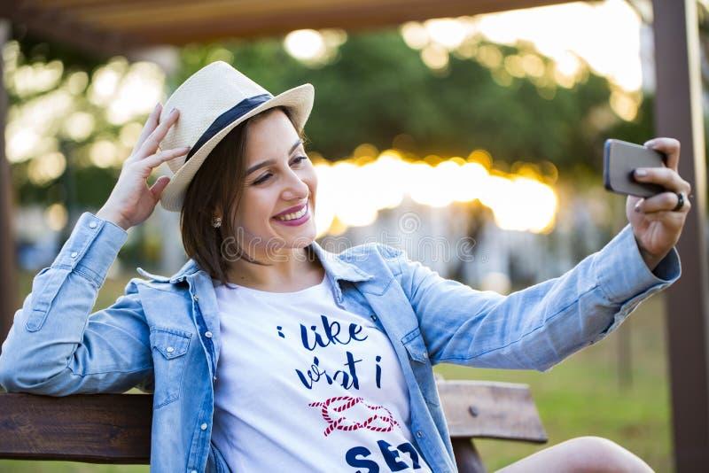 A menina que senta-se no parque e faz o selfie, feliz fotos de stock