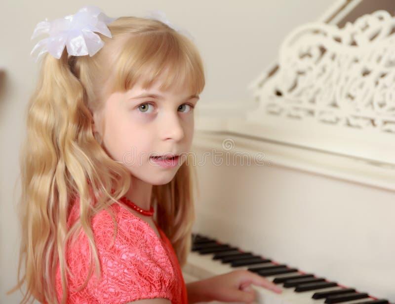Menina que senta-se no piano imagem de stock