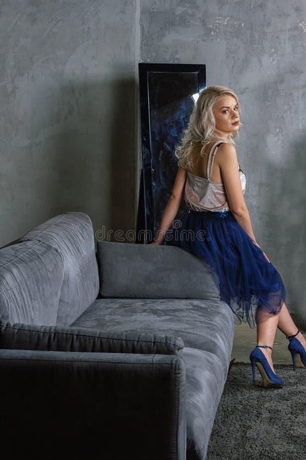 Menina que senta-se no sofá imagem de stock royalty free