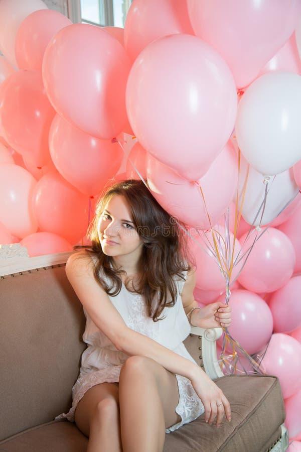 Menina que senta-se no sofá com lotes dos balões fotografia de stock royalty free