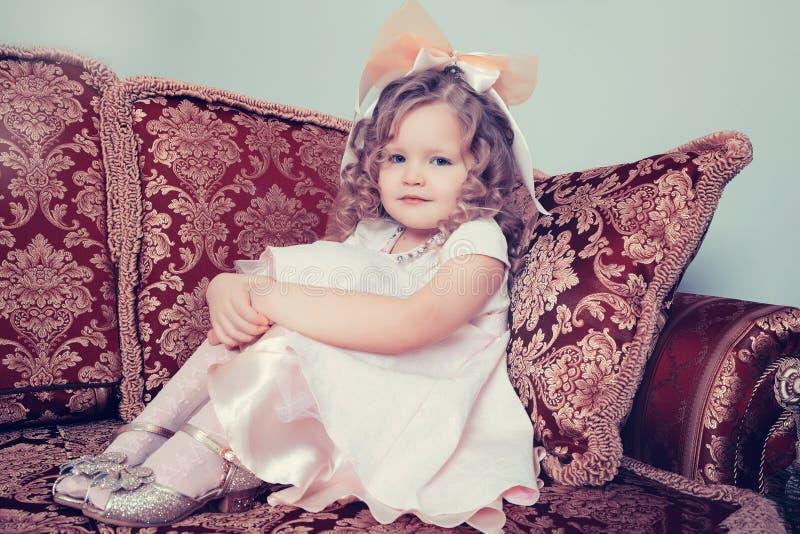 Menina que senta-se no sofá que abraça seus joelhos com suas mãos fotografia de stock