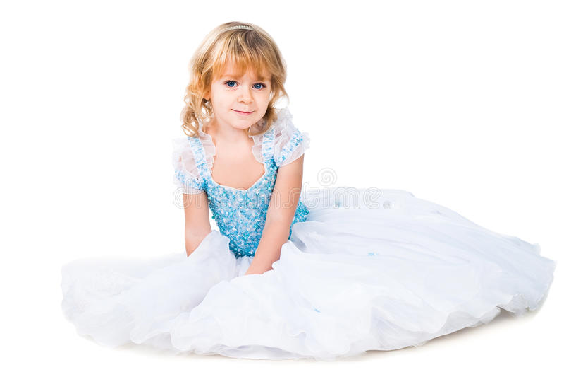 Menina que senta-se no vestido azul lindo no branco fotografia de stock