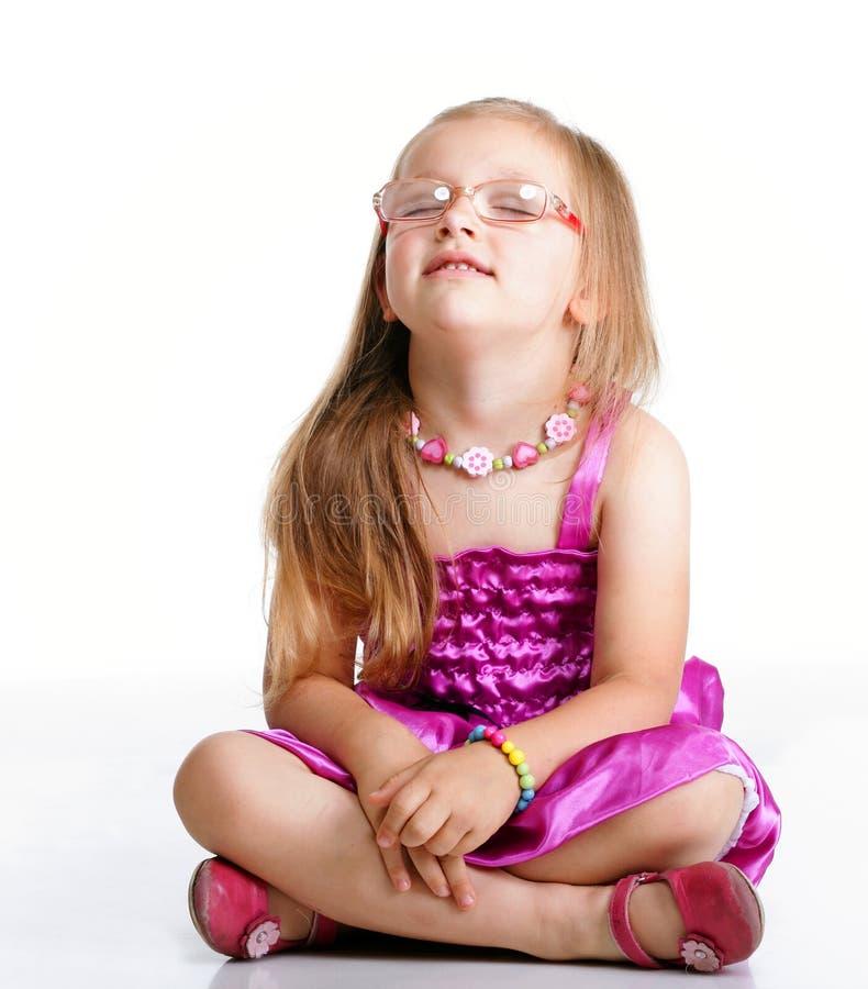 Menina que senta-se nos olhos fechados do assoalho isolados foto de stock royalty free