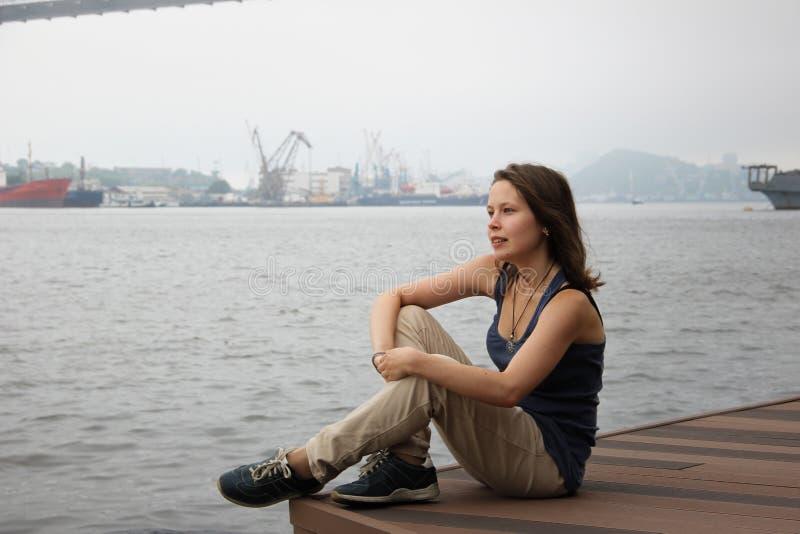 Menina que senta-se olhando o mar imagem de stock