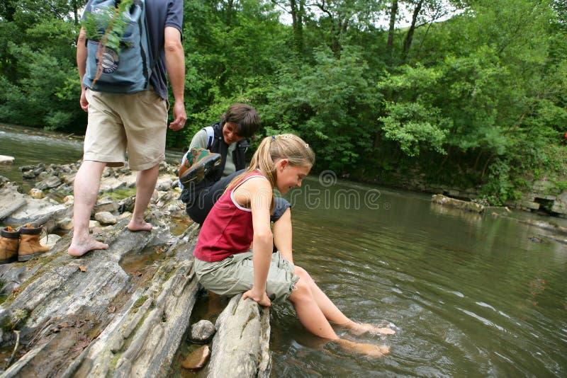 Menina que senta-se pelo rio com pais imagens de stock royalty free