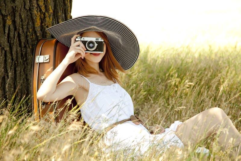 Menina que senta-se perto da árvore com câmera do vintage. imagem de stock