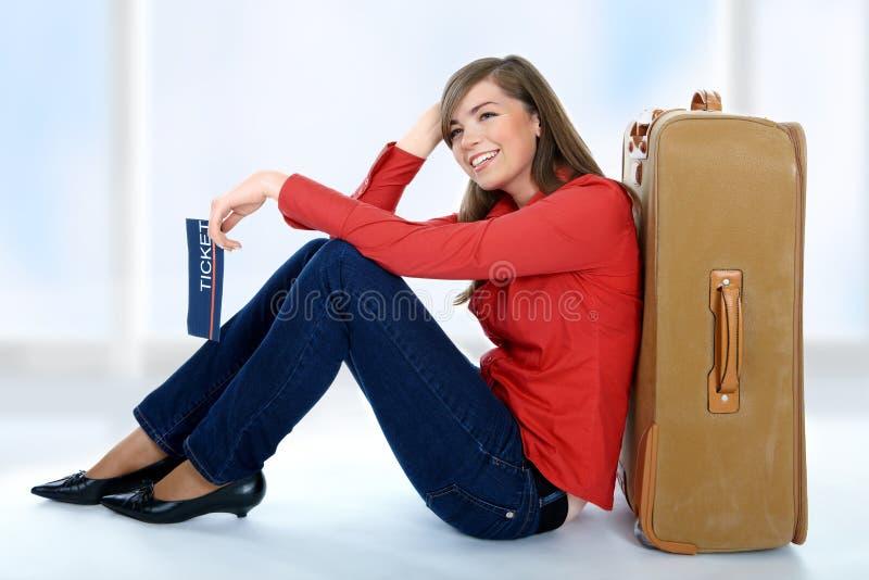 Menina que senta-se perto de uma mala de viagem fotografia de stock royalty free