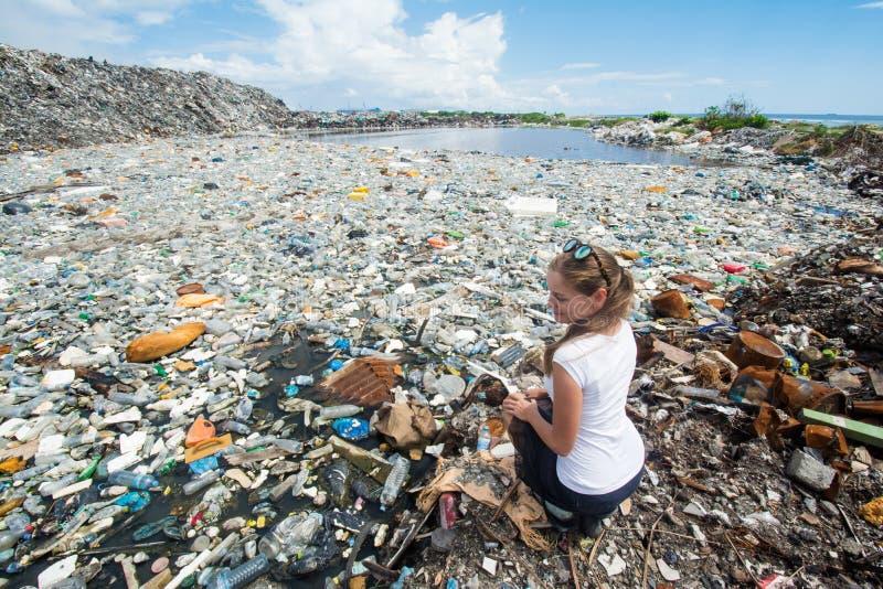 Menina que senta-se perto do lago coberto com as garrafas plásticas imagens de stock