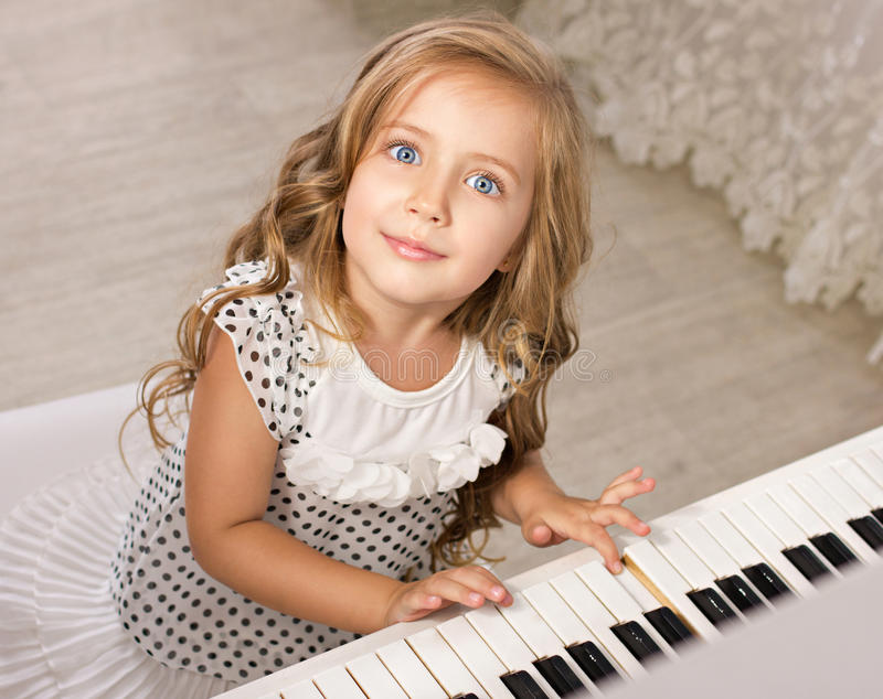 Menina que senta-se perto do piano imagens de stock
