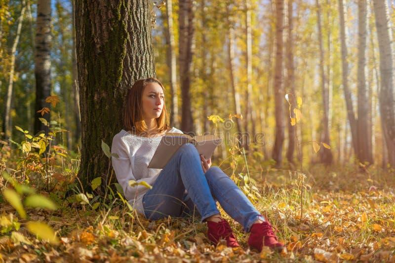 Menina que senta-se sob uma árvore com um livro imagem de stock royalty free