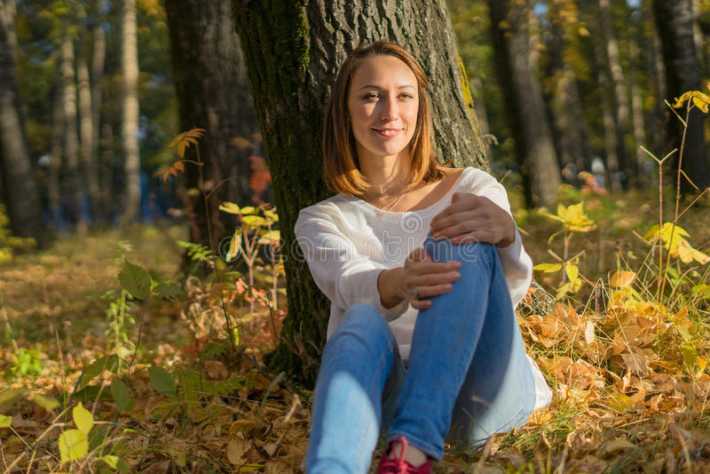 Menina que senta-se sob uma árvore na floresta imagens de stock royalty free