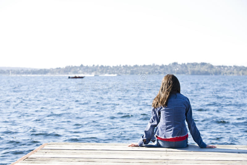 Menina que senta-se sozinho na doca pelo lago imagem de stock