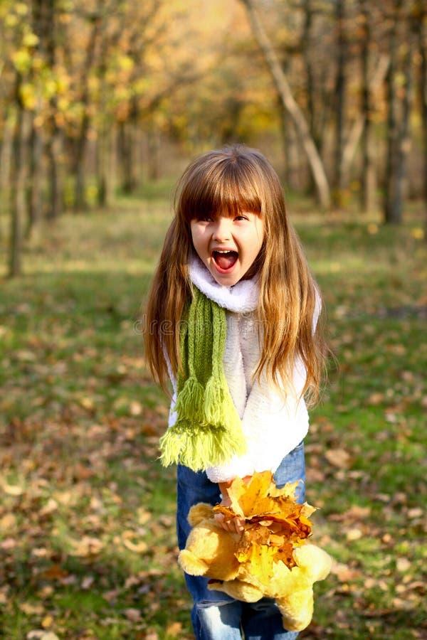 Menina que shouting e que prende as folhas imagem de stock