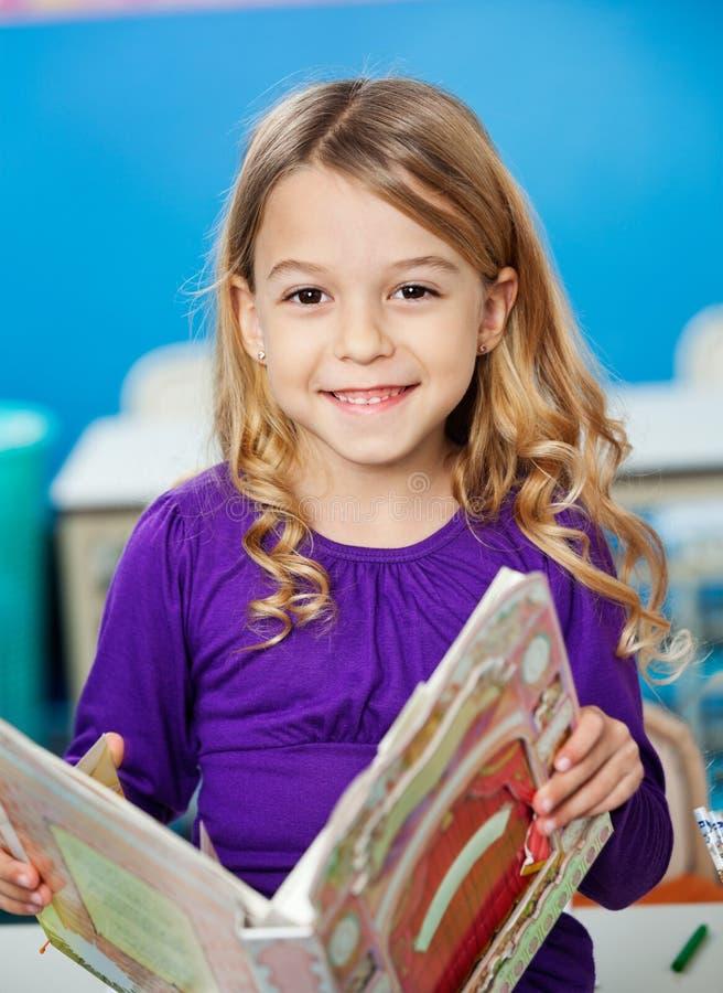 Menina que sorri ao guardarar o livro no jardim de infância fotografia de stock royalty free