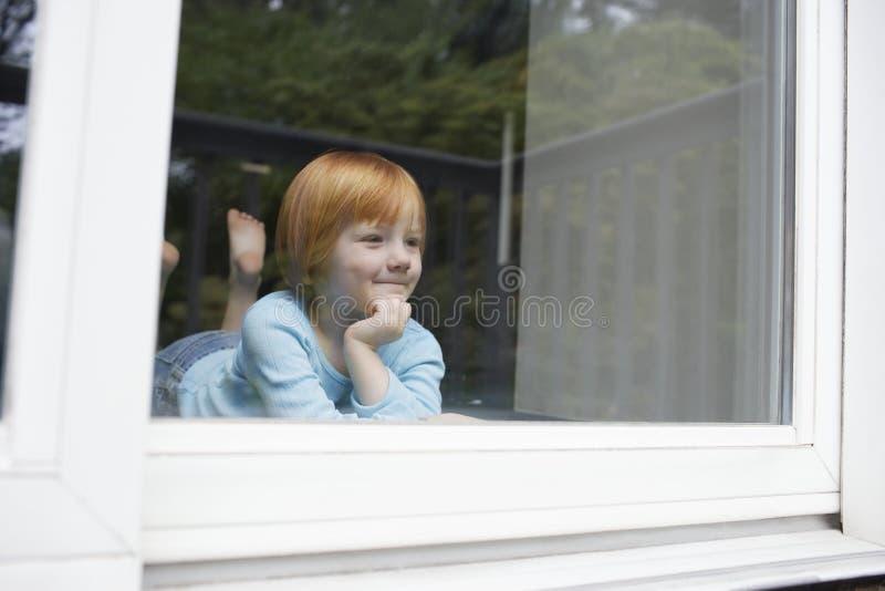 Menina que sorri ao olhar para fora através da janela de vidro fotografia de stock