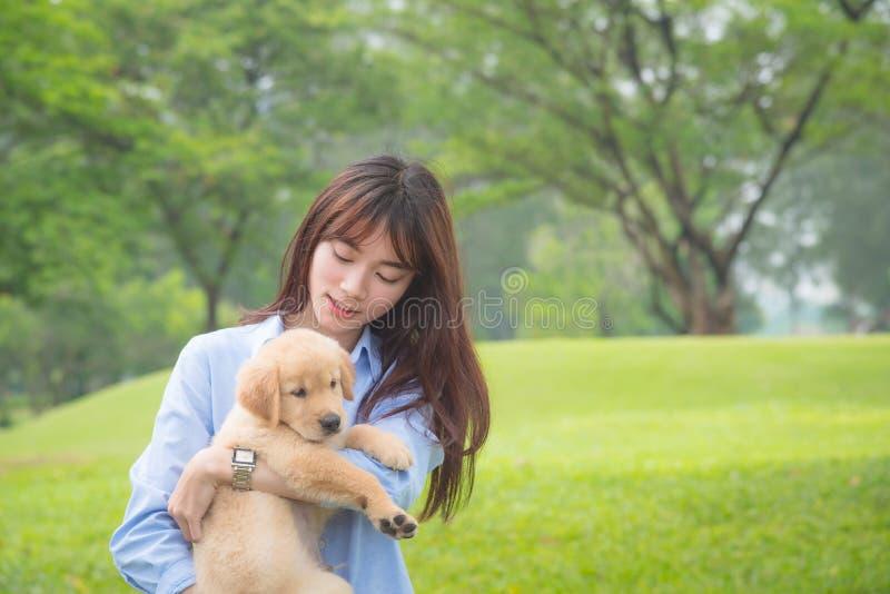 Menina que sorri com seu cão pequeno no parque imagens de stock royalty free