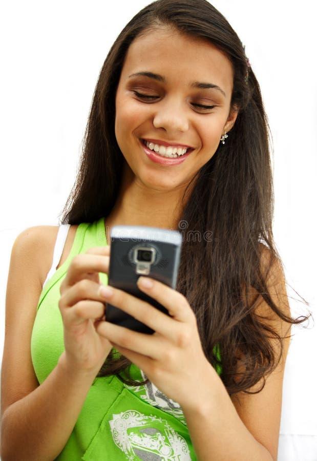 Menina que sorri com seu telemóvel fotografia de stock royalty free