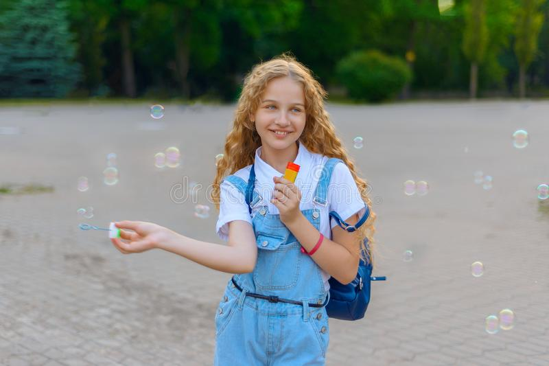 Menina que sorri e feliz fundir bolhas foto de stock