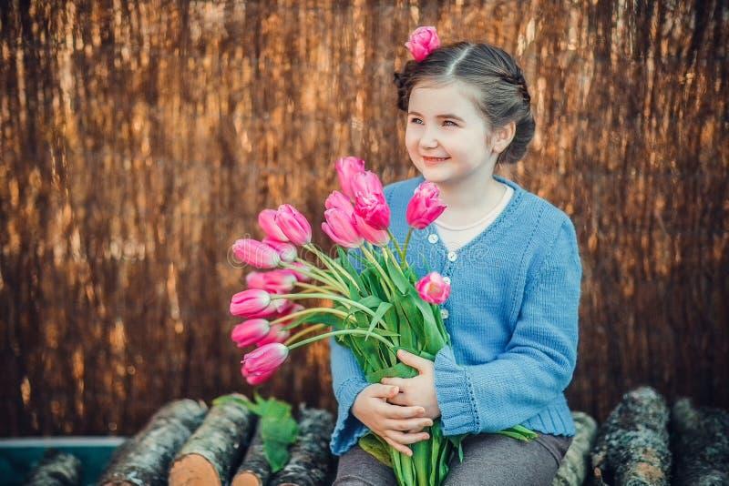 Menina que sorri felizmente com flores cor-de-rosa imagem de stock