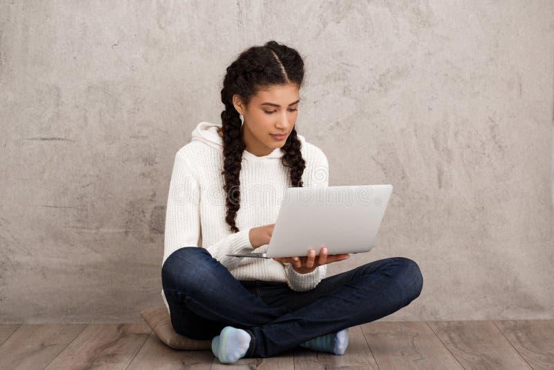 Menina que sorri, guardando o portátil, sentando-se no assoalho sobre o fundo bege imagem de stock