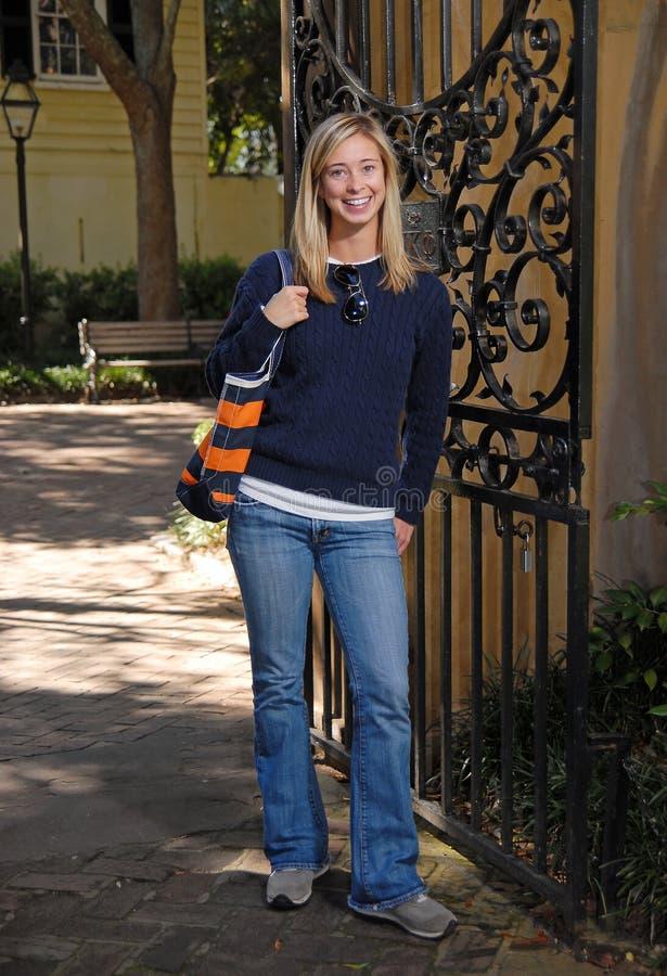 Menina que sorri pela porta na queda foto de stock royalty free