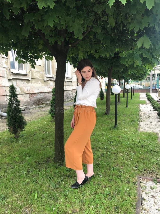 Menina que sorri perto de uma árvore de florescência Retrato exterior de uma senhora bonita nova da forma que levanta perto de um foto de stock royalty free