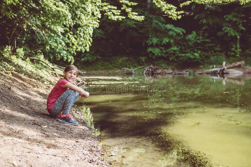 Menina que squatting pelo lago imagens de stock