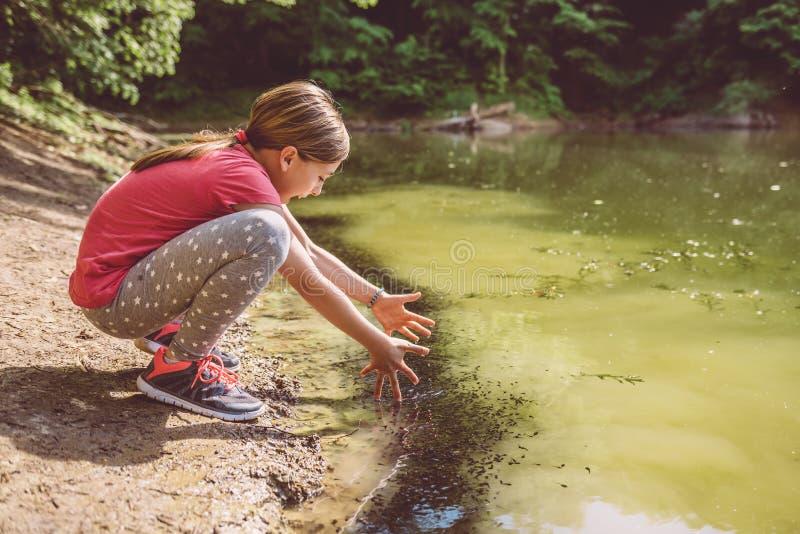 Menina que squatting pelo lago fotos de stock