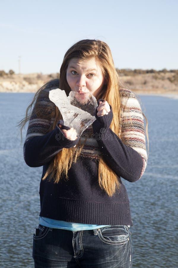 Menina que suga em uma parte grande de gelo no lago congelado foto de stock royalty free