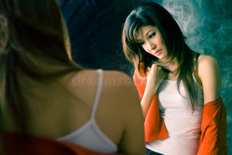 Menina que tem a doença da insónia na frente de um espelho