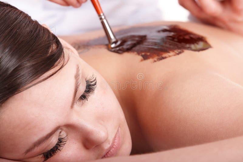 Menina que tem a máscara do corpo do chocolate. imagens de stock royalty free